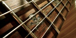 Guitar with skull and crossbones design on fret